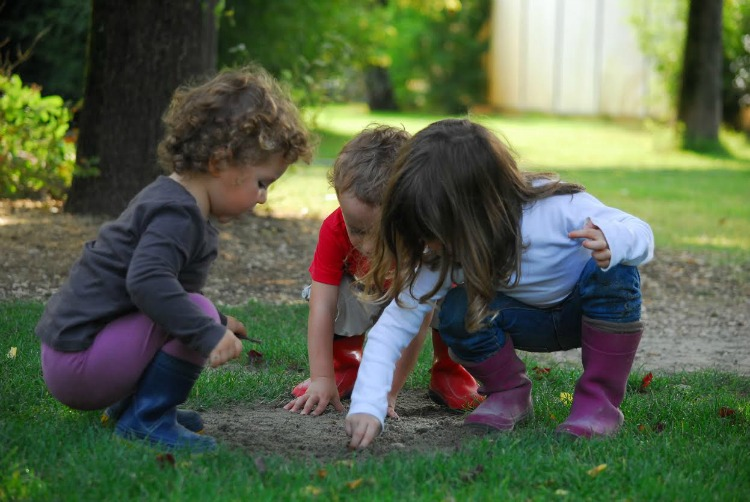 children playing with sand in garden