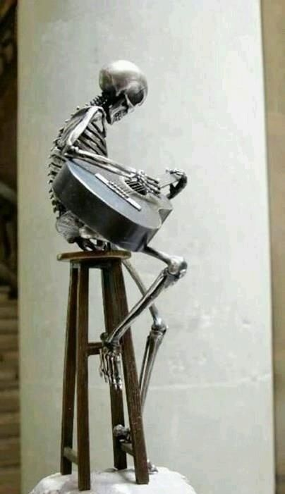 skeleton playing guitar metal sculpture